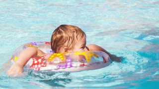 Kid learns to swim using a plastic water ring in the swimming pool or waterpark