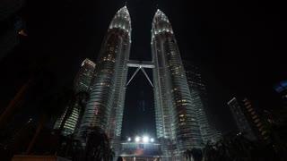 KUALA LUMPUR, MALAYSIA - NOVEMBER 05, 2015: Hyperlapse low angle shot of walking at the bottom of illuminated Petronas Twin Towers at night