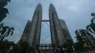 KUALA LUMPUR, MALAYSIA - NOVEMBER 05, 2015: Timelapse low angle shot of people at Petronas Twin Towers getting illuminated at night