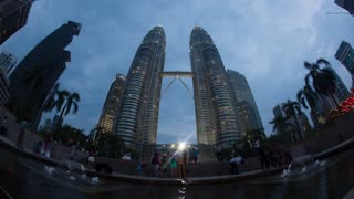 KUALA LUMPUR, MALAYSIA - NOVEMBER 05, 2015: Timelapse wide and low angle shot of people in front of Petronas Twin Towers illuminated at night