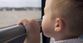 Little boy is looking out the window of moving bus. He is pointing at something interesting and smiling