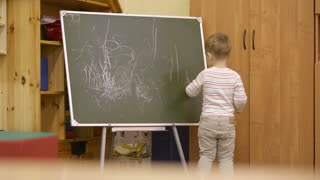Little boy standing with his back to the camera drawing on a chalkboard at kindergarten during class as he expresses his creativity