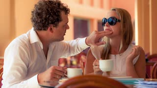 Lovely couple in a cafe having tea. Man cleaning womans face while she making funny grimace