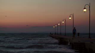 Man walking along the pier with lanterns, some people standing in the distance. Strong sea waves striking pier