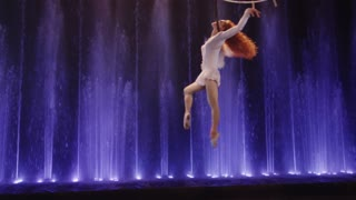 MOSCOW, RUSSIA - FEBRUARY 21, 2011: Slow motion shot of aerial performance of a woman acrobat with neck loop in the Circus of Dancing Fountains Aquamarine