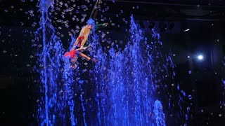 MOSCOW, RUSSIA - FEBRUARY 21, 2015: Slow motion and handheld shot of children gymnasts performing on the rope in the air against bright spolight. Fairy-tale performance with bubbles in the Circus of Dancing Fountains Aquamarine