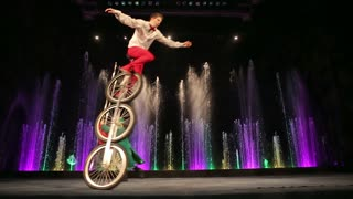 MOSCOW, RUSSIA - FEBRUARY 21, 2015:  Young man balancing on three wheeled cycle and doing tricks with plates. Exciting performance in the Circus of Dancing Fountains Aquamarine