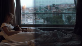 Mother and son lying in bed under blanket. They having fun and looking at the evening city through the window