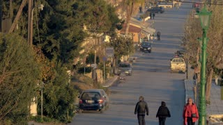 NEA KALIKRATIA, GREECE - JANUARY 13, 2016: Street in small town. Few cars on the road and few people walking there
