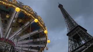 PARIS, FRANCE - SEPTEMBER 06, 2015: Low angle shot of illuminated vintage carousel spinning by the Eiffel Tower, the main city landmark. Shot in the evening against cloudy sky