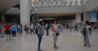 PARIS, FRANCE - SEPTEMBER 06, 2015: People in the underground hall of Louvre Pyramid with following view of glass construction