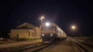 Passenger train leaving small rural station at night.