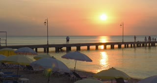People are walking along the pier at sunset, everyday life of beach resort