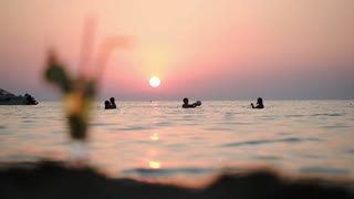 People swimming and playing in the sea with following focus on mojito standing by the water on the beach. Sunset in background