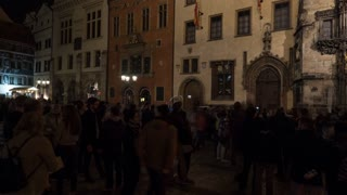 PRAGUE, CZECH REPUBLIC - APRIL 28, 2016: Timelapse panning shot of people coming to see Prague astronomical clock at night. The third-oldest astronomical clock in the world and the oldest one still