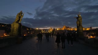 PRAGUE, CZECH REPUBLIC - APRIL 28, 2016: Tourists and locals walk across the Charles bridge in the evening. Historic bridge crosses the Vltava river constructed in the beginning of the 15th century