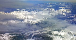 Scenic top view from the flying airplane. Beautiful grand mountains with snowy tops and thin clouds