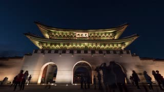 SEOUL, SOUTH KOREA - OCTOBER 22, 2015: Timelapse low angle shot of people walking through and making photos of illuminated Gwanghwamun Gate at night. City landmark