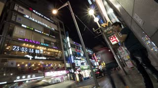 SEOUL, SOUTH KOREA - OCTOBER 22, 2015: Timelapse panning shot of people and cars on night street. Buildings illuminated with store banners