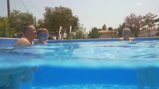Slow motion clip of a little boy learning swimming underwater in the pool with his grandpa, mum and grandma. Beautiful scene with blue sky and green trees in background