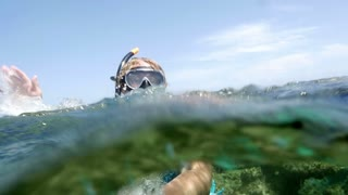 Slow motion clip of a senior woman diver in snorkel waving with the hand from clear sea water on background of clear blue sky. Recreation and tourism