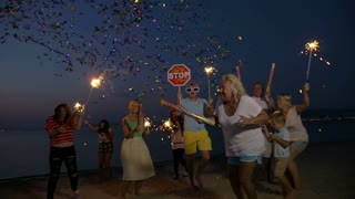Slow motion clip of happy and excited people celebrating New Year or Christmas on the beach at night. They having fun and dancing with sparklers and confetti crackers