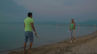 Slow motion clip of young man and woman playing badminton on the beach in the evening. People having fun on summer holidays. Endless sea and city lights in background