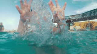 Slow motion of a child playing in the pool. Happy boy having fun on vacation. Close-up shot of water splashes