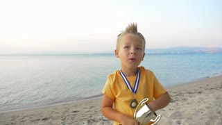 Slow motion of a little boy jumping and getting excited with the victory. He holding a cup and wearing a medal. Winner emotions, shot on the background of sea and sky