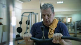 Slow motion of a mature man having hard workout on pull down machine. Getting fit in modern fitness center