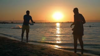 Slow motion of young man and woman playing tennis by the sea at sunset. Golden sun reflecting in dark water. Active and carefree summer vacation
