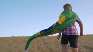 Slow motion shot of a boy with flag of Brazil tied as cape running away on the sand and celebrating the victory standing on sky background. Summer Olympic Games in Rio 2016