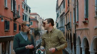 Slow motion shot of a young couple standing outdoor in Venice, Italy wearing Venetian carnival masks. They are kissing, smiling and throwing confetti.