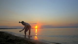 Slow motion steadicam shot of a young sportsman performing acrobatics at the seaside at sunset. He doing somersaults and falling into the water at the end