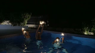 Slow motion steadicam shot of happy family or three friends enjoying the time in the swimming pool at night. They waving sparklers celebrating Christmas or New Year