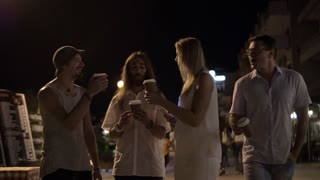 Slow motion steadicam shot of happy friends of three man and a woman toasting with take-away coffee cups. They laughing, drinking coffee and walking in night city street