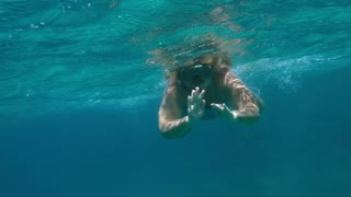 Slow motion underwater shot of a woman swimming with a snorkel in Red Sea. She is waving with her hand to the camera.