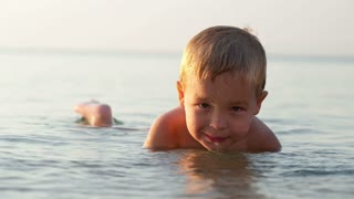 Smiling little boy ducking down in the shallow water at the seaside in a tranquil ocean on a summer day