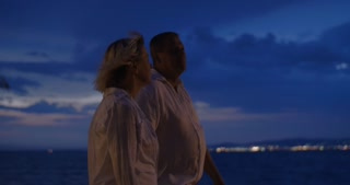 Steadicam shot of a senior family couple enjoying evening outing by the waterside.  They walking against background of dark cloudy sky and sea