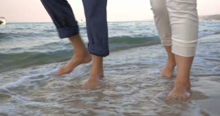 Steadicam shot of bare feet of two people walking along the sea in incoming waves