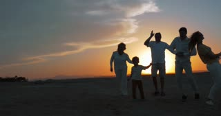 Steadicam shot of parents, little child and grandparents spending evening on the beach. They dancing on the sand against bright sunset. Happy family vacation