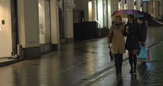 Steadicam shot of young women walking  under colorful umbrella in evening rainy city and having a talk after good shopping