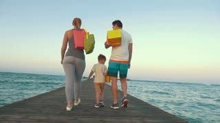 Steadicam slow motion shot of a family walking on the sea pier and holding shopping bags. They are turning to the camera and waving hands.