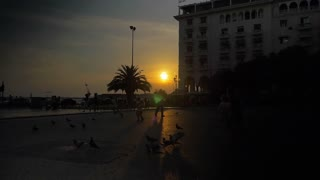 THESSALONIKI, GREECE - AUGUST 15, 2015: Slow motion clip of people on the city square at sunset. Girls chatting to each other and passing by, children playing with pigeons