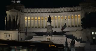 Tilt shot of a woman coming up to the road and taking a picture of Altar of Fatherland at night. Female tourist using touch pad to capture landmarks of Rome