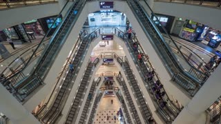 Timelapse high angle shot of modern multistorey shopping mall. People traffic on the escalators of each floor. Trade centre in Petronas Twin Towers in Kuala Lumpur, Malaysia