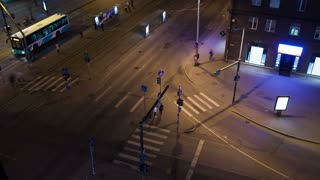 Timelapse of night Tallin with its city traffic. High angle view of crossroad with zebra crossings and tram stop