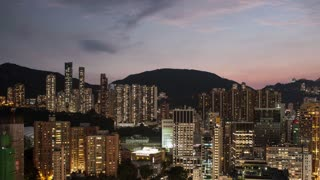 Timelapse panning shot of Hong Kong at night. City with illuminated buildings, roads and football fields