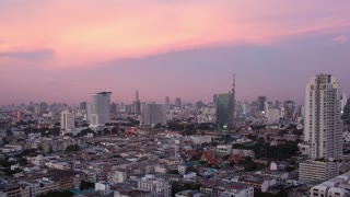 Timelapse panning shot of night changing evening in Bangkok, Thailand. Panoramic city view with transport traffic
