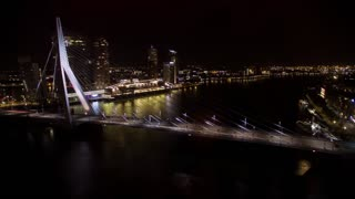 Timelapse shot of car traffic on illuminated Erasmus Bridge and boats sailing down the river in Rotterdam, view at night